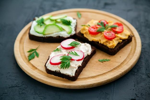 Вкусные вегетарианские тосты из ржаного хлеба с творогом, хумусом, авокадо, редисом и помидорами на деревянной доске