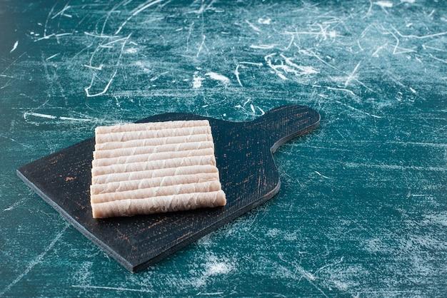 Tasty wafer rolls on black cutting board.
