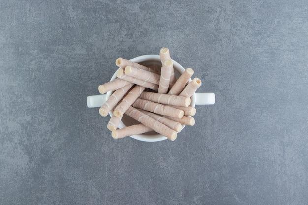Rotoli saporiti del wafer in ciotola bianca.