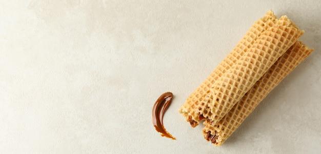 Вкусные вафельные трубочки со сгущенкой на белой текстуре
