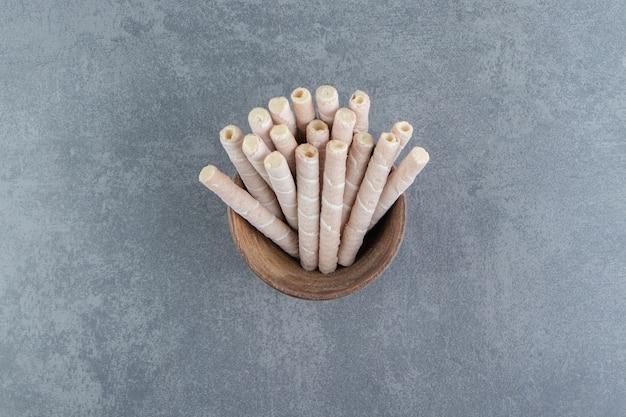 Rotoli di wafer gustosi in ciotola di legno.