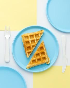 Вкусная вафля на синей детской тарелке, вид сверху