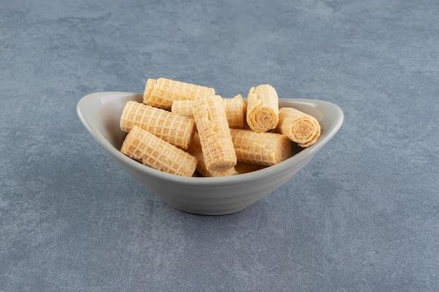 Tasty waffle rolls in ceramic bowl.