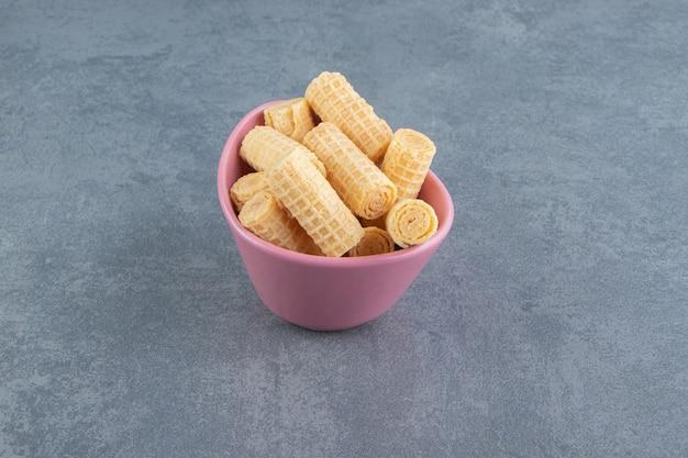 ピンクのボウルに美味しいワッフルが巻かれています。