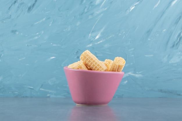ピンクのボウルに美味しいワッフルが巻かれています。 無料写真
