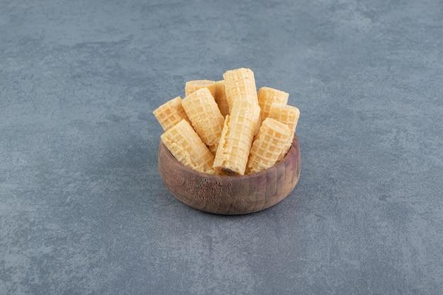 おいしいワッフルは木製のボウルに巻かれています。 無料写真