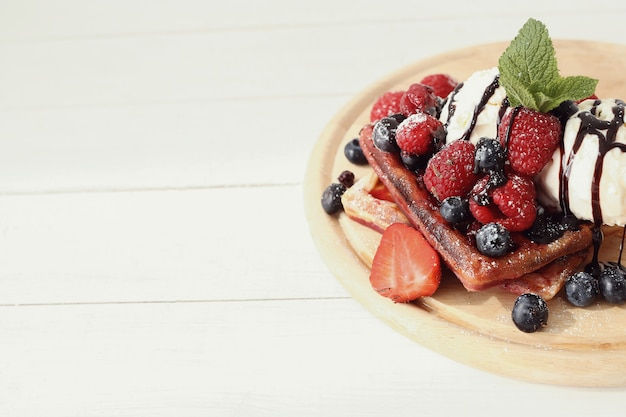 Tasty waffle with blueberries and strawberries