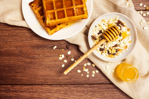 Tasty waffle with healthy oats and honey on wooden table