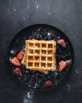 Tasty waffle with strawberries and sugar, top view