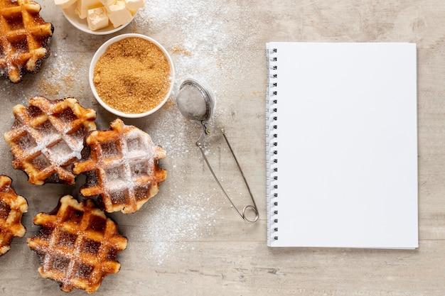 Tasty waffles sugar and a notebook