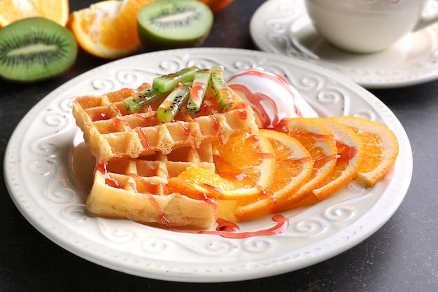 하얀 접시에 맛있는 과일, 아이스크림, 시럽으로 맛있는 와플