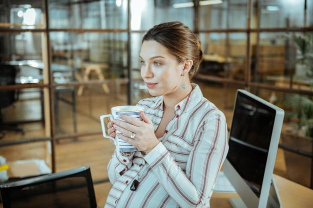Вкусный теплый чай. привлекательная беременная женщина пьет вкусный теплый чай в офисе после рабочего времени