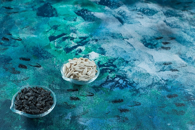 Вкусные белые и черные семечки в стеклянных мисках на синем столе.
