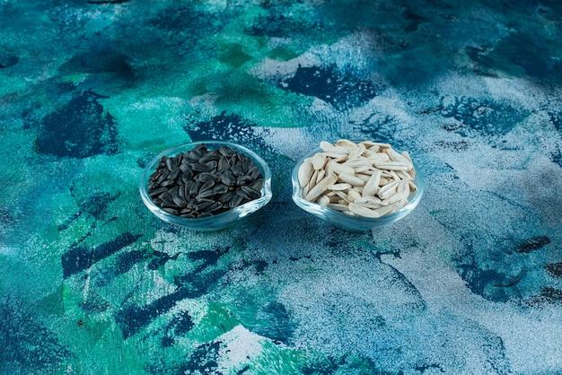青いテーブルの上のガラスのボウルに、おいしい白と黒のヒマワリの種。