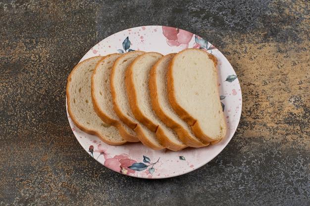 カラフルなプレートにおいしい白パンのスライス