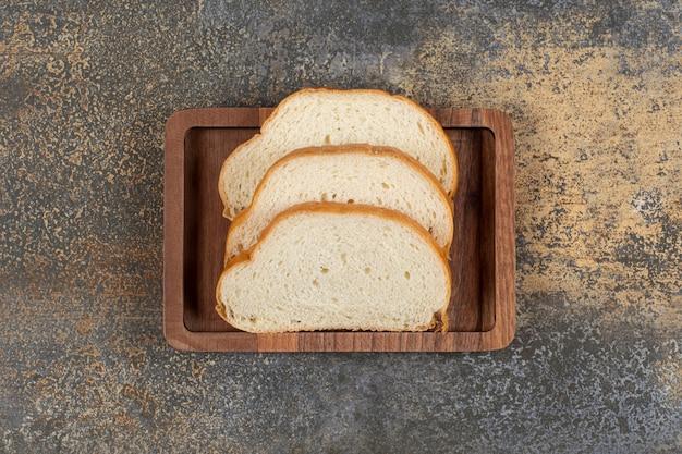 나무 접시에 맛있는 흰 빵 조각.