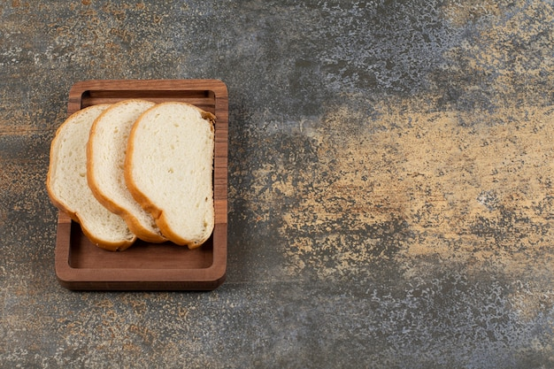 Tasty white bread slices on wooden plate.