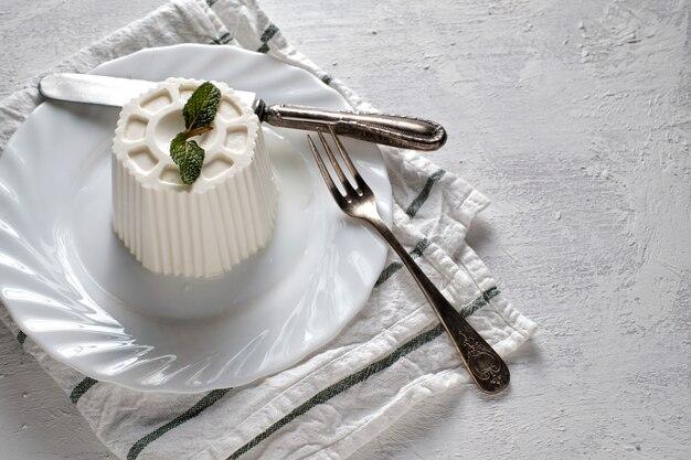 Вкусный белый сыр с листьями мяты на тарелке