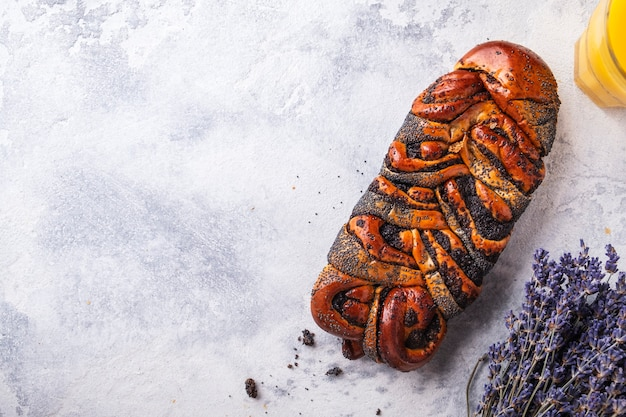 Tasty wicker bun  poppy seeds and orange juice. top view.