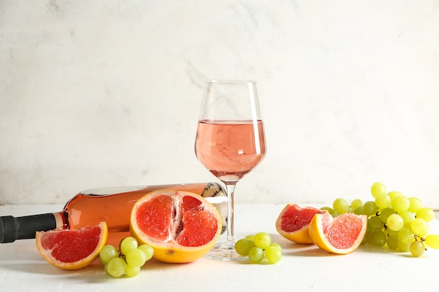 Tasty wine with fresh fruits on white table