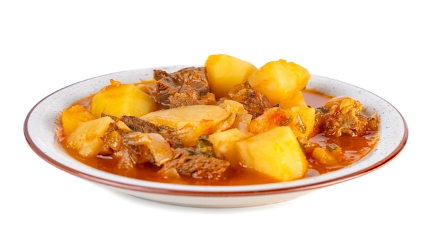 Tasty winter stew with meat and vegetables on a plate with ingredients isolated on white background.