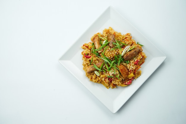 야채와 쇠고기 회색 테이블에 하얀 접시에 새 콤 하 고 달콤한 소스에 맛있는 웍 쌀. 복사 공간이있는 평면도