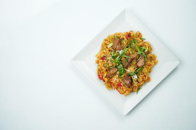 회색 테이블에 하얀 접시에 야채와 돼지 고기와 달 콤 하 고 신 소스에 맛있는 웍 쌀. 복사 공간이있는 평면도