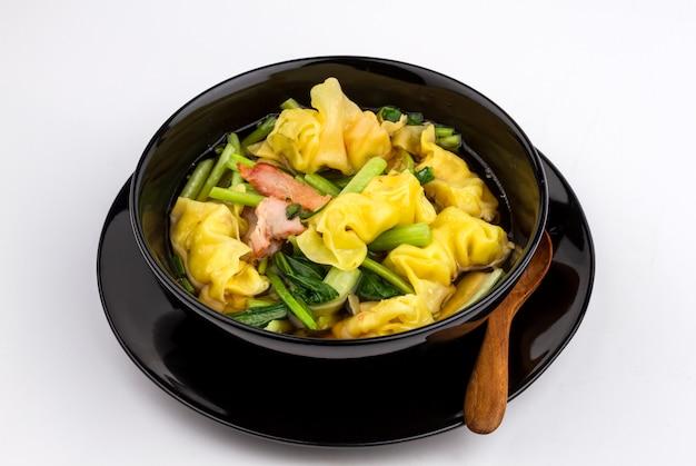 Tasty wonton soup in black bowl