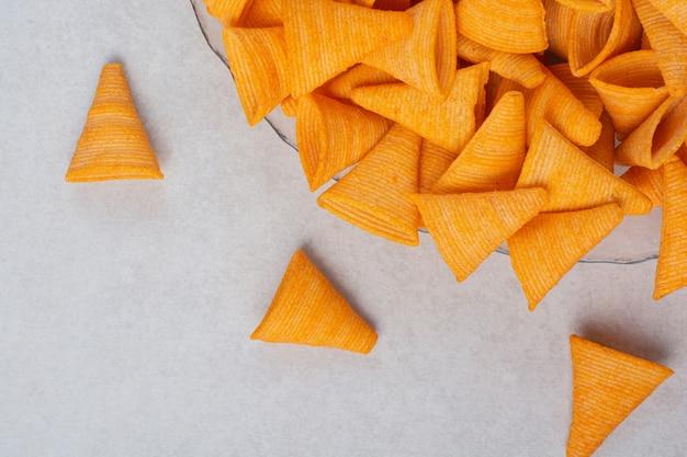 Вкусные желтые хрустящие чипсы на белом фоне. фото высокого качества