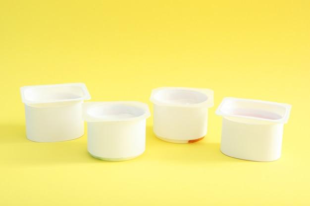 テキストを挿入するための色付きのテーブルの場所にあるプラスチックガラスのおいしいヨーグルト