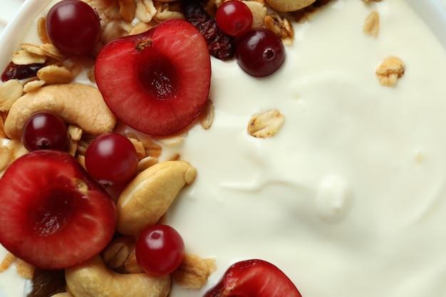 Tasty yogurt with different ingredients, close up