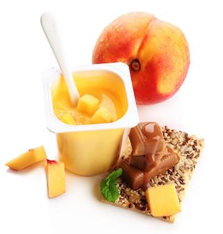 흰색에 신선한 과일, 쿠키 및 토피 사탕의 조각과 맛있는 요구르트