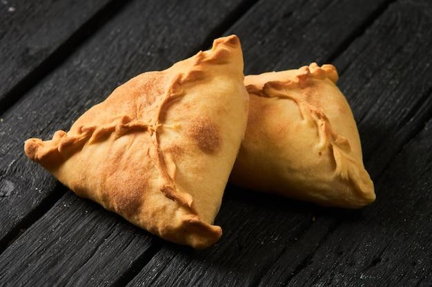 타타르 파이 삼각형 echpochmak, 러시아 kurnik, 닭고기와 감자를 곁들인 맛있는 생과자. 전통 음식, 반죽의 빠른 간식.