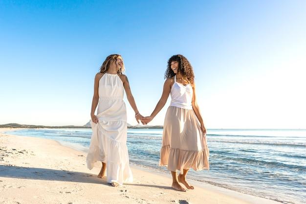 Татуированная красивая блондинка молодая кавказская женщина смеется, держа за руку свою чернокожую латиноамериканскую подругу, идущую на берегу моря утром или на закате
