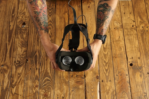 Tattoed hands hold vr glasses upside down, presentation of new technology, isolated on rustic wooden board