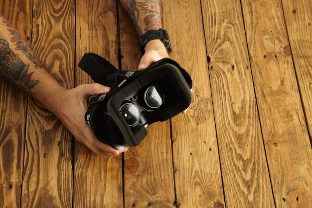 Tattoed hands hold vr glasses upside down, presentation of new technology