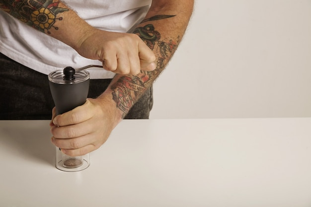 A tattoed man in white t-shirt and black jeans grinds coffee beans in a modern slim manual burr grinder, close up