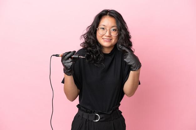 Азиатская женщина татуировщика изолирована на розовом фоне, показывая большой палец вверх жест