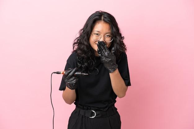 ピンクの背景に分離されたタトゥーアーティストアジア人女性幸せと笑顔の手で口を覆う