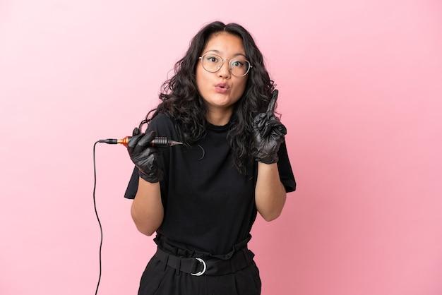 Азиатская женщина-татуировщик изолирована на розовом фоне, намереваясь реализовать решение, подняв палец вверх