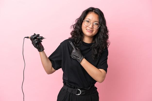 Азиатская женщина-татуировщик изолирована на розовом фоне, указывая в сторону, чтобы представить продукт