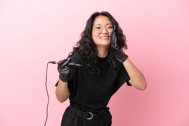 Азиатская женщина татуировщика изолирована на розовом фоне кричит с широко открытым ртом