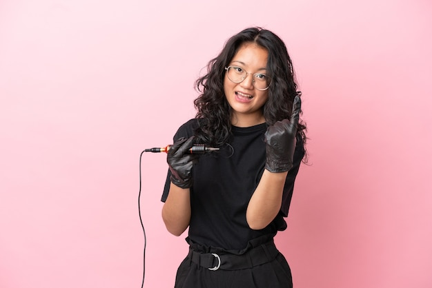 Tattoo artist asian woman isolated on pink background doing coming gesture
