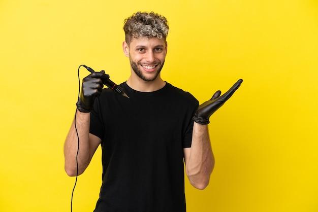 Художник-татуировщик кавказский мужчина изолирован на желтом фоне, протягивая руки в сторону, приглашая приехать