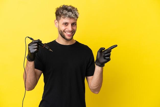 Кавказский мужчина татуировщик изолирован на желтом фоне, указывая пальцем в сторону