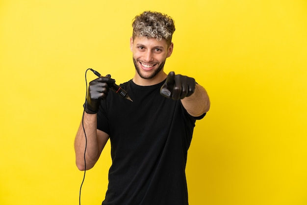 Кавказский человек татуировщика изолирован на желтом фоне, указывая на фронт со счастливым выражением лица