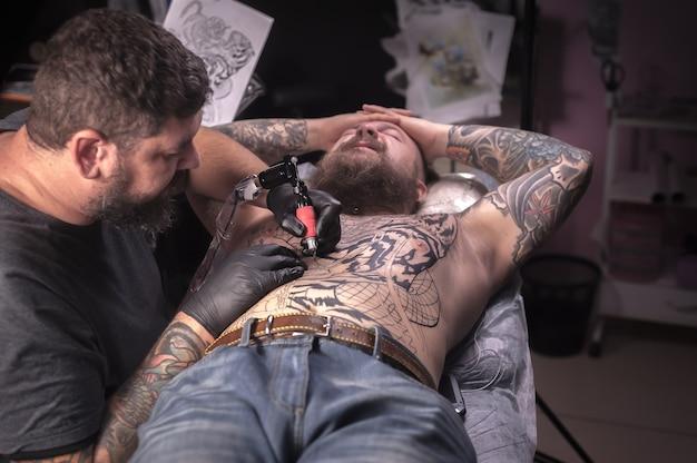 Художник-татуировщик делает татуировку на коже своего клиента в мастерской-студии.