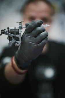 Tatuatore tenendo e guardando una macchina per tatuaggi