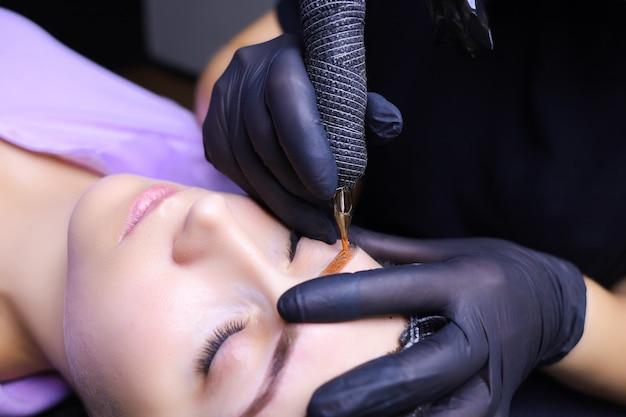 Художник-татуировщик в черных перчатках с тату-машинкой для нанесения пигмента на брови клиента.