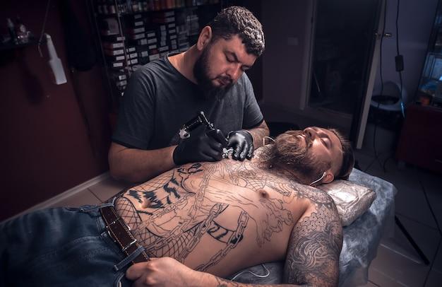 タトゥーアーティストはタトゥースタジオでタトゥー写真を作ります。